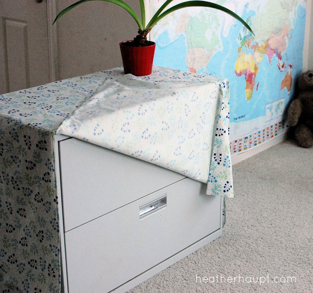 Get creative by covering a filing cabinet with fabric to hide the office look. :)